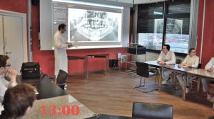 Ärzte während einer Präsentation. Ein Arzt steht vor einer Leinwand. Auf der Leinwand ist ein Ultrschallbild  zu erkennen.