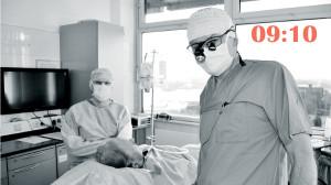 Zwei Personen mit Kittel, Muschutz und Opperationshaube, Auf einem Bett liegt ein Patient.
