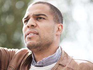 Ein Mann in brauner Lederjacke deutet mit dem Arm in eine Richtung.