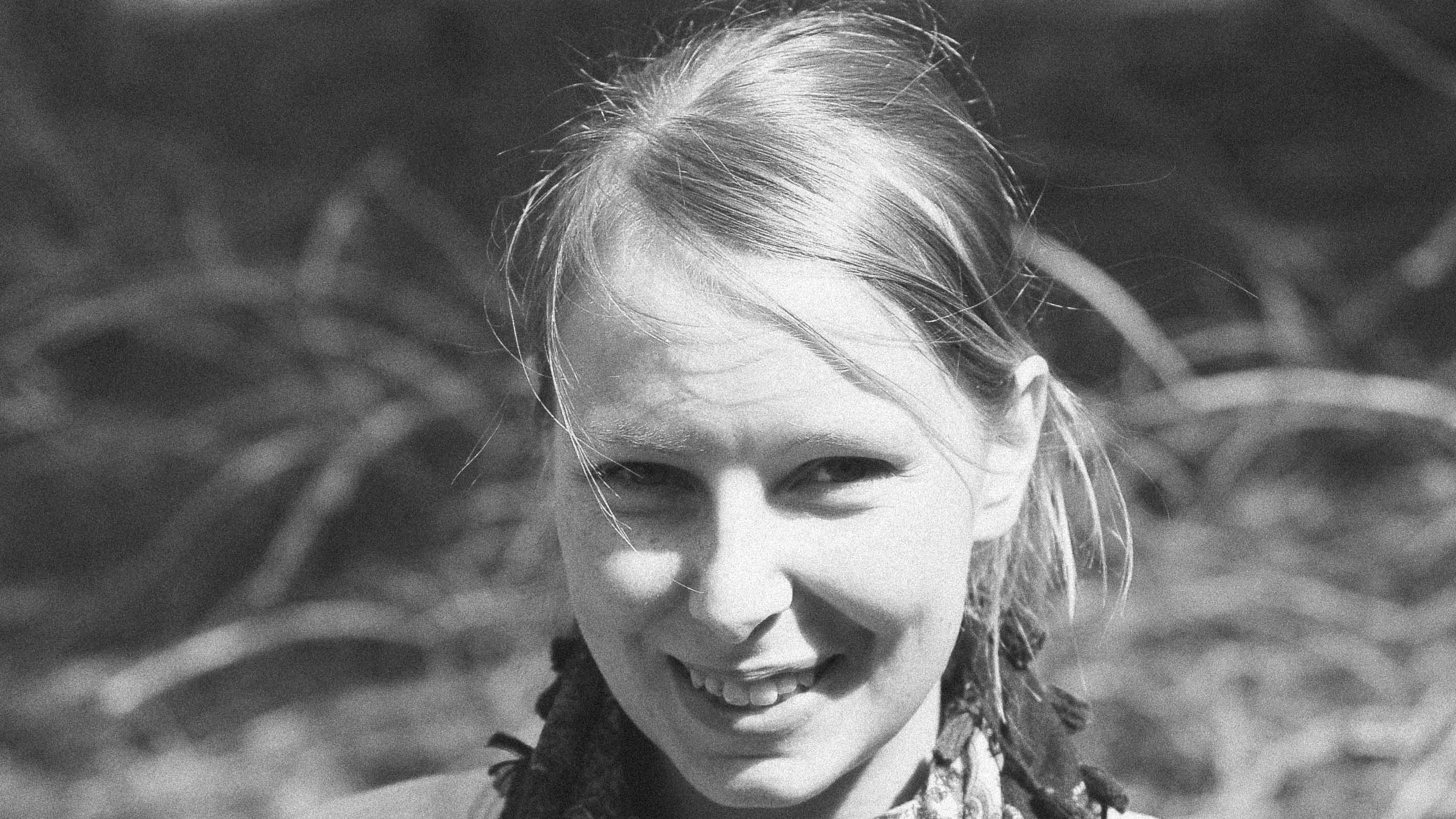 Eine blonde junge Frau lächelt in die Kamera.
