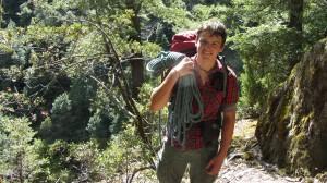 Ein junger Mann in Wanderausrüsttung lächelt in die Kamera.