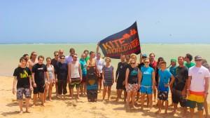 Kite-surfer stehen zusammen am Strand.