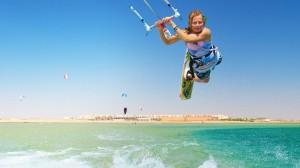 Eine junge Frau lässt sich von einem Kite-Schirm in die Luft ziehen.