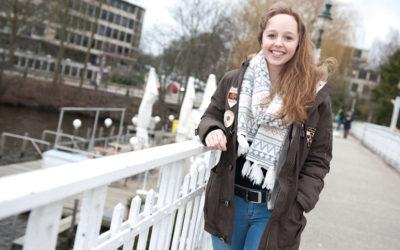 Eine junge Frau schlendert lachend über eine Brücke.