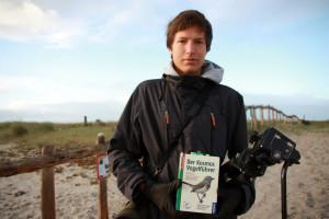 Ein junger Mann in dunkler Jacke hält ein Fernglas und ein Buch zur Vogelerkennung in die Kamera.