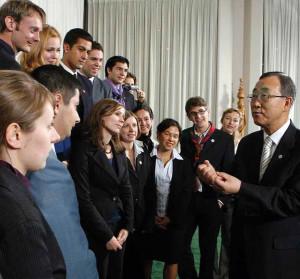 Ein asiatischer Mann im Anzug steht vor einer Gruppe lächelnder junger Menschen.