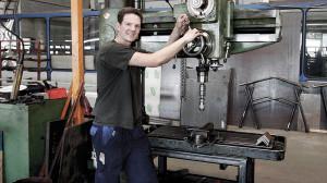 Ein junger Mann in einer Werkstatt arbeitet mit einer Stnadbohrmaschine.