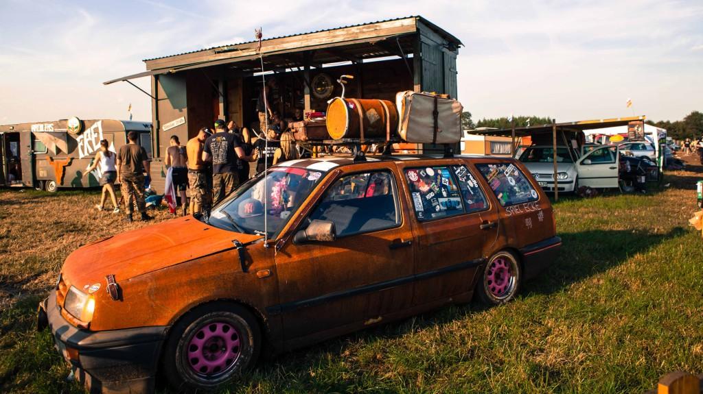 Ein PKW-Kombi steht vor einer selbstgebauten BÜhne auf einem Feld.