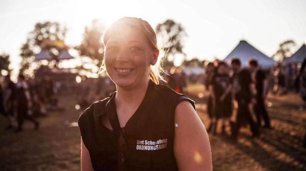 Eine junge Frau in schwarzer Weste lächelt in die Kamera. Im Hintergrund ist die Sonne zu sehen.
