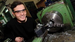 Ein junger Mann mit Schutzbrille steht lächelnd an einer Werkbank.