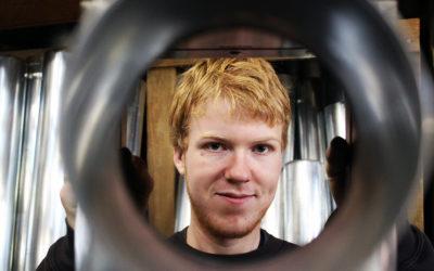 Ein blonder junger Manns schaut durch ein Metallrohr.