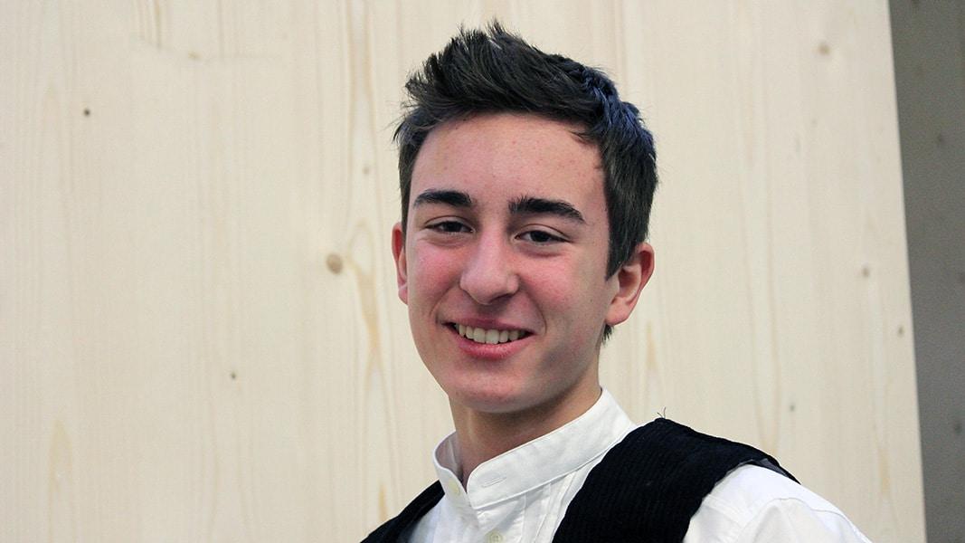 Ein dunkelhaariger junger Mann in Weste steht vor einer Holzwand.