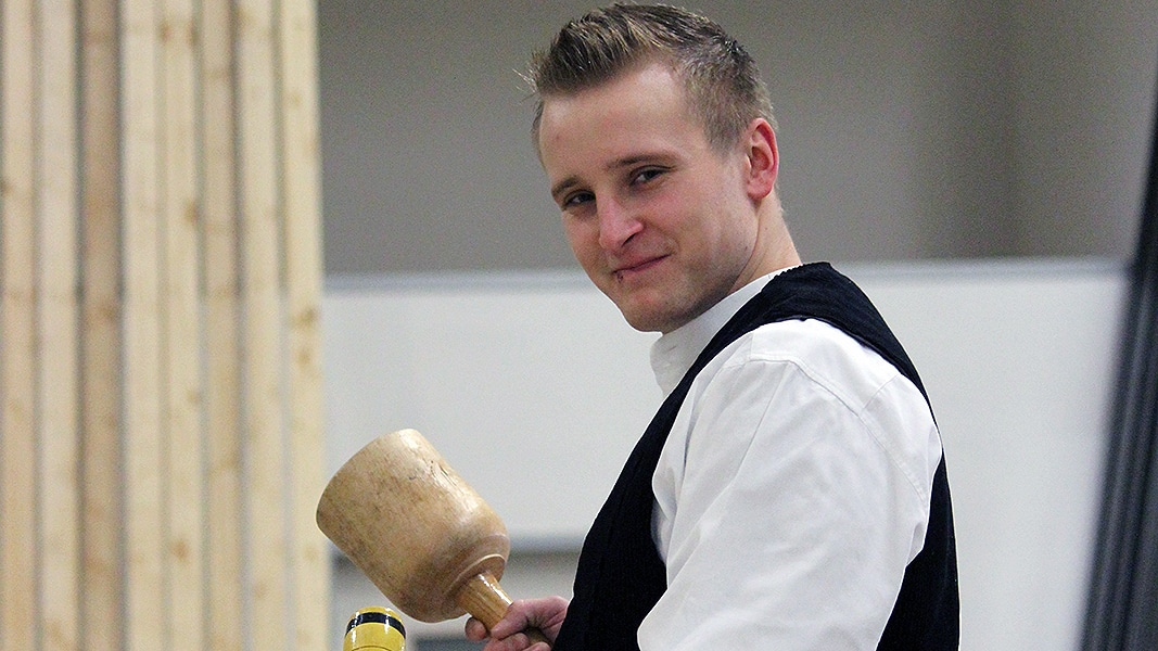Ein blonder junger Mann steht mit einem Holzhammer vor einer Holzwand.