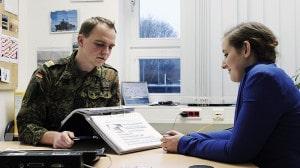Eine junge Frau sitzt bei einem Berufsberater der Bundeswehr im Büro.