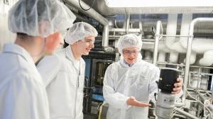 Drei Menschen in weißer Arbeitskleidung in einer Fabrik