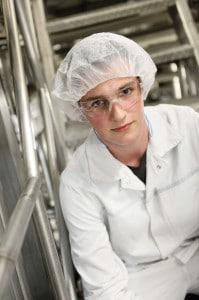 Ein Mitarbeiter in einem Meiereibetrieb in weißer Arbeitskleidung