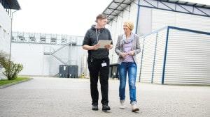 Zwei junge Erwachsene gehen vor einem Fabrikgebäude.