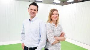 Ein Mann und eine Frau stehen Rücken an Rücken in einem Green-Screen-Studio und lächeln in die Kamera.