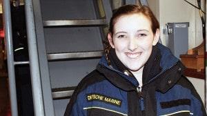 Eine junge Frauen Uniform lächelt in die Kamera.