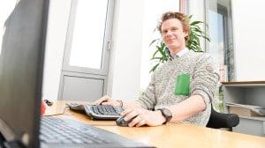 Ein rothaariger Mann sitzt an einem Rechner.