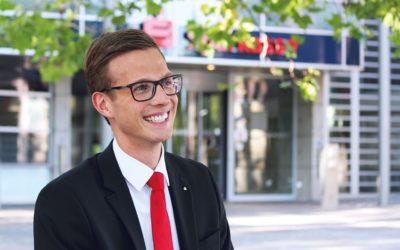 Eine junger Mann im Anzug und mit roter Krawatte.