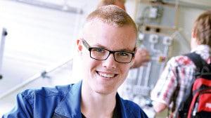 Ein bebrillter junger Mann im blauen Hemd und kurzen Haaren lächelt in die Kamera.