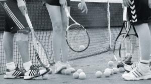 Die Füße und Tennisschläger dreier Sportler auf einem Tennisplatz.