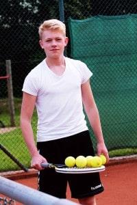 Ein jugendlicher balanciert Tennisbälle auf einem Schläger.