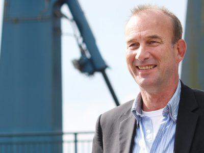 Ein Mann in einem Jackett lächelt vor einem blauen Kran.