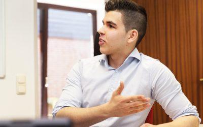 Ein junger Mann sitzt gestikuliernd an einem Tisch