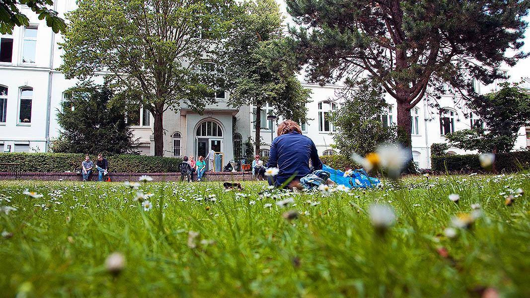 Eine Studierende sitzt auf einem grünen Rasen.