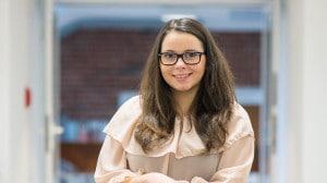 Eine junge Frau mit Brille lächelt in die Kamera.