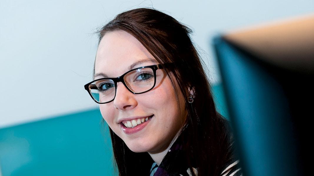 Eine brünette junge Frau mit Brille lächelt in die Kamera.
