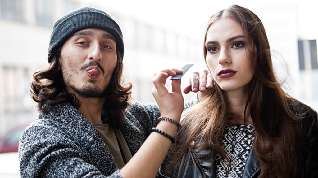 Ein Mann schminkt eine Frau. Dabei streckt er die Zunge heraus.