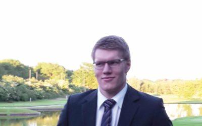 Ein junger Mann im dunklen Anzug blickt in die Kamera.
