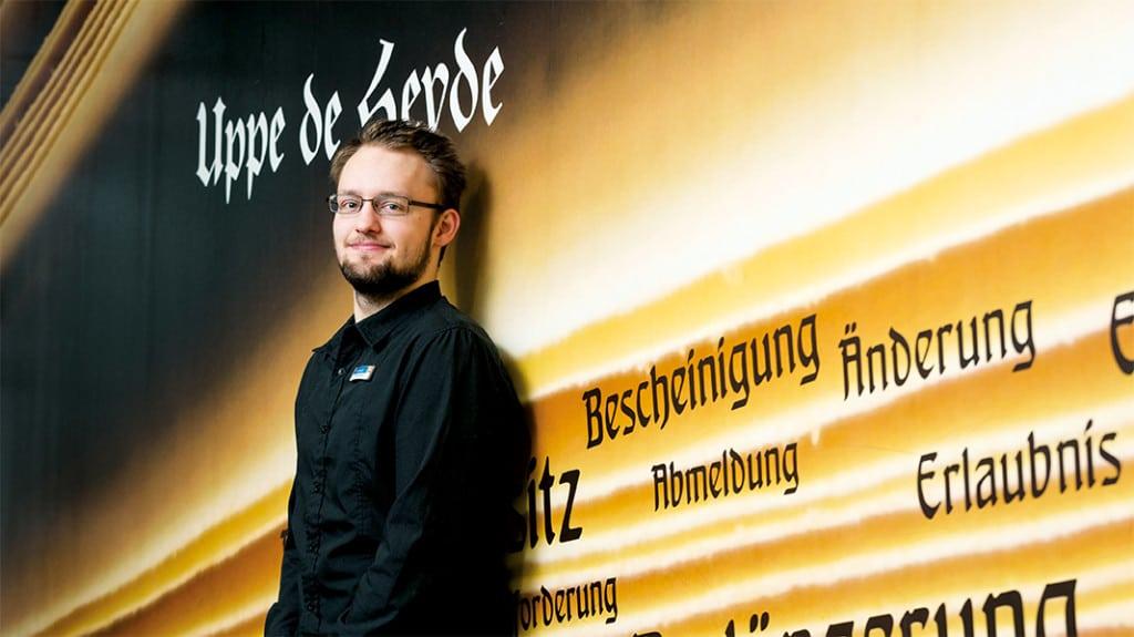 Ein junger Mann mit Brille und mit schwarzem Hemd steht vor einer Wand.