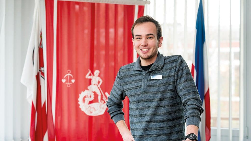 Ein junger Mann in grauem Pulli steht vor einem Wappen.