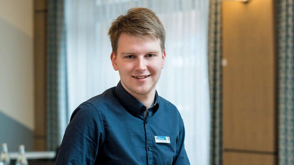 Ein junger Mann in blauem Hemd lächelt in die Kamera.