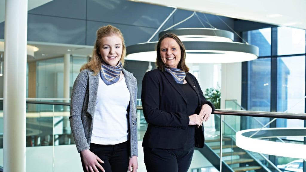 Zwei Frauen stehen nebeneinander vor einer Glaswand und lächeln in die Kamera.