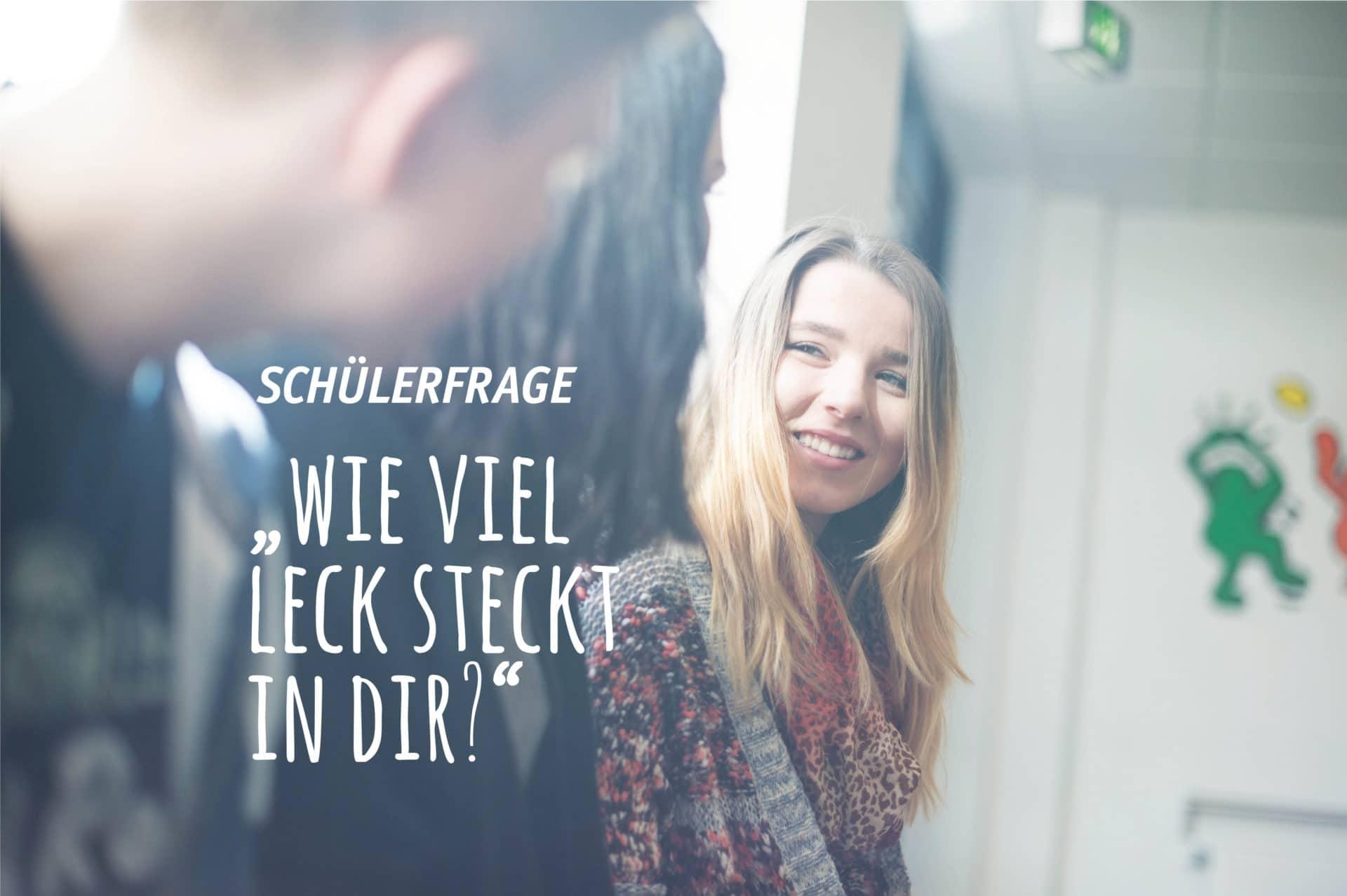 Eine blonde jugendliche lächelt einen, dem Betrachter abgewandten, Jugendlichen an.