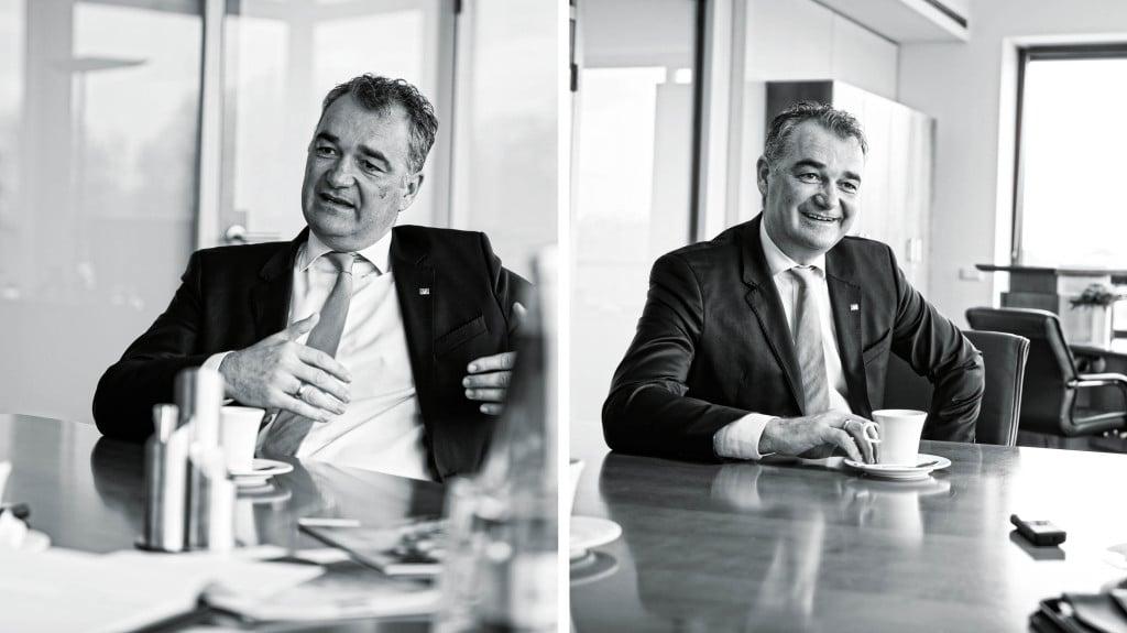 Eine Collage, bestehend aus zwei Bildern, zeigt den selben Mann während eines Interviews an einem Tisch sitzend.