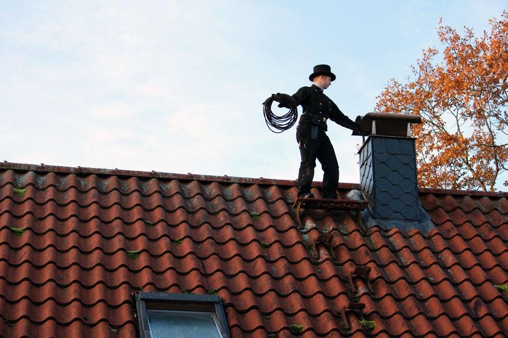 Schornsteinfegerin Nina bei der Arbeit auf dem Dach