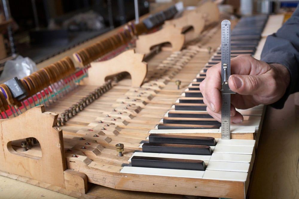 Klavier-, und Cembalobauer bei der Arbeit