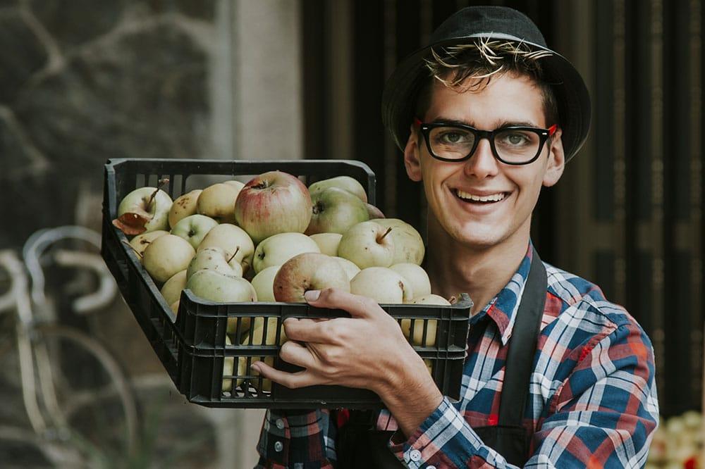 Einzelhandelskaufmann mit einer Kiste Äpfel