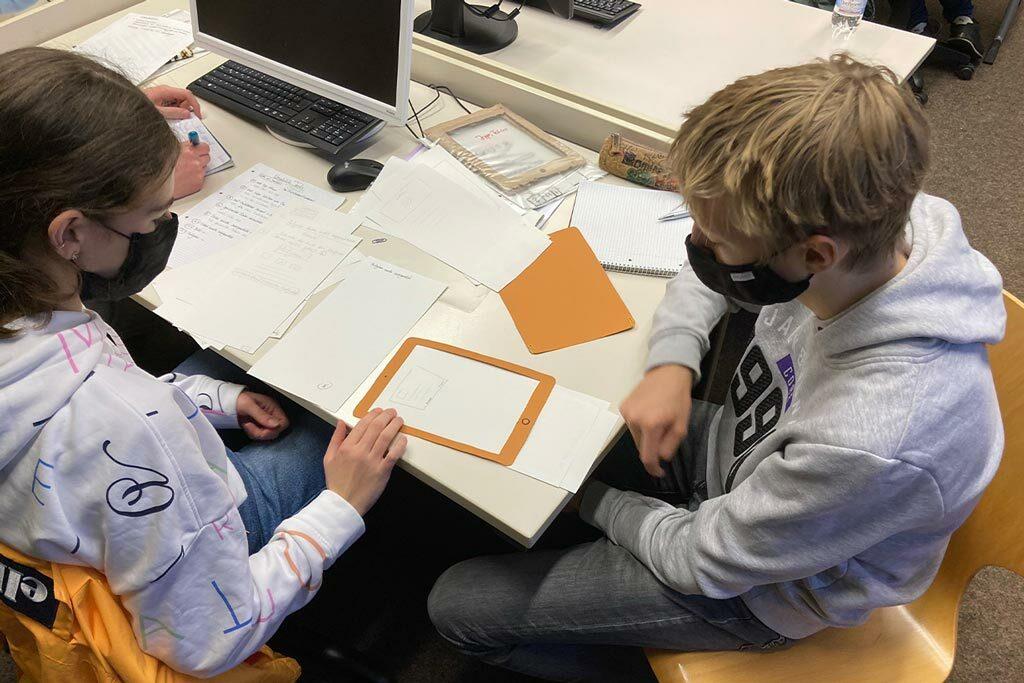 Schüler planen mit Schere und Papier ein App Design